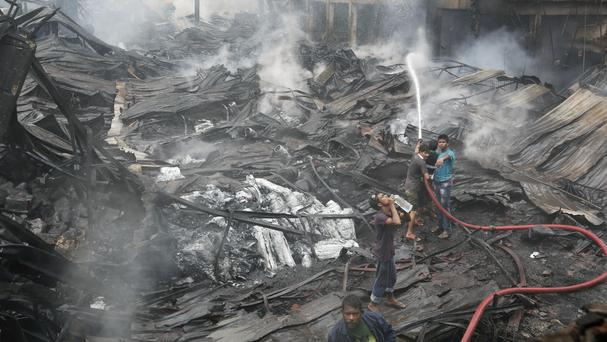 Firefighters work to put out the blaze at a packaging factory in the Tongi industrial area (AP)
