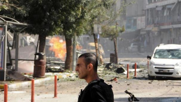 A security member stands after a car bomb attack in the city centre of Van, eastern Turkey (AP)