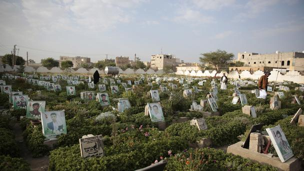 Yemenis offer prayers at the portrait adorned graves of their relative who were killed in the ongoing conflict (AP)