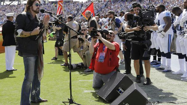 Tennessee Titans players, including Wesley Woodyard, far right; Jason McCourty, second from right; and Jurrell Casey, third from right; stand during the singing of the national anthem by Billy Ray Cyrus