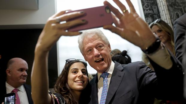 Former President Bill Clinton pauses for a selfie with a supporter at a coffee shop while campaigning for his wife, Hillary, in Los Angeles (AP)