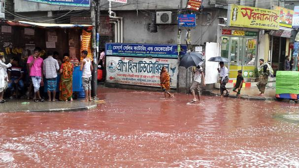 People wade past a road turned red after blood from sacrificial animals mixed with water from heavy rainfall in Dhaka, Bangladesh (AP)