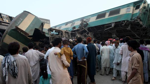 People look at a train that collided with a freight train near Multan, Pakistan (AP)