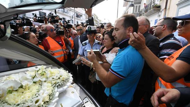 Members of the media crowd around the hearse during the funeral of Tiziana Cantone (ANSA/AP)