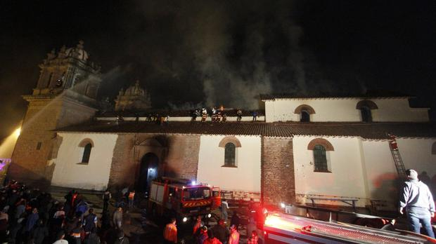 Firefighters work to extinguish a blaze at the famed 16th century San Sebastian church in Cuzco, Peru (AP)