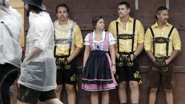 People wait outside a tent during heavy rain ahead of the Oktoberfest beer festival in Munich (AP)