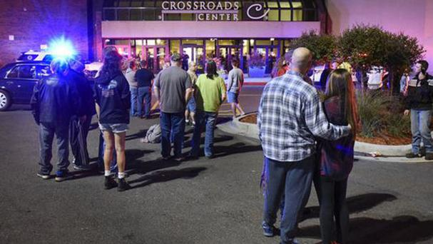 People outside the Minnesota shopping centre where multiple people were injured in a stabbing incident (St Cloud Times/AP)