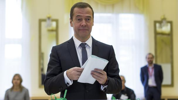 Russian prime minister Dmitry Medvedev holds his ballot paper at a polling station during a parliamentary elections in Moscow (AP)