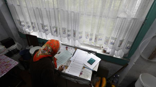 A woman reads her ballot papers in the village of Gusino, outside Smolensk (AP)