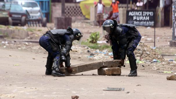 Riot police remove a slab of rock used to block a road during a protest in Kinshasa (AP)
