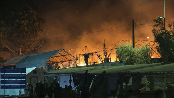 Riot police stand guard as a large fire burns inside the Moria refugee camp on the north-eastern Greek island of Lesbos (AP)