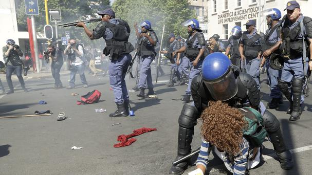 A female student is arrested as police fired stun grenades and rubber bullets in an attempt to disperse them during a protest, in Johannesburg (AP)