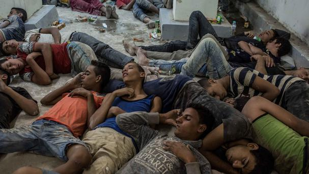 Migrants detained at a police station sleep on the floor in Rosetta after being rescued from a boat capsized off Alexandria (AP)