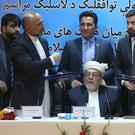 Amin Karim, representative of Gulbuddin Hekmatyar, right, and Afghanistan national security adviser Mohammad Hanif Atmar, third left, hold their documents after signing a peace deal, in Kabul (AP)