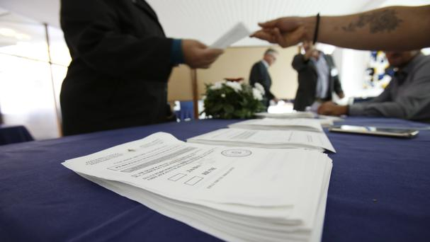 A Bosnian Serb woman with her ballot paper at a polling station (AP)