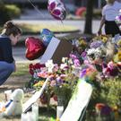 A member of the public places a tribute at a memorial to the victims of the Cascade Mall massacre (AP)