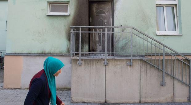 A woman walks in front of the entrance to the mosque in Dresden, Germany (Sebastian Kahnert/dpa via AP)