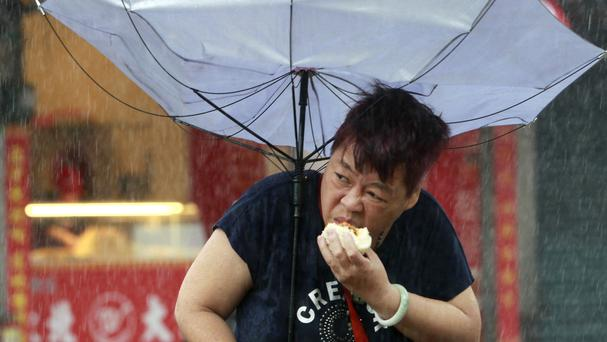 A woman struggles with her umbrella against powerful gusts of wind generated by typhoon Megi across Taiwan (AP)