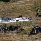 Rescue workers stand arround the debris of the crashed Swiss army helicopter in the Alps (AP)