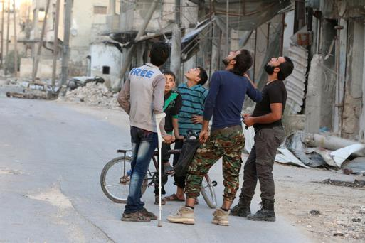 People look at the sky fearing an airstrike in a rebel-held part of Aleppo. Pictures: Reuters