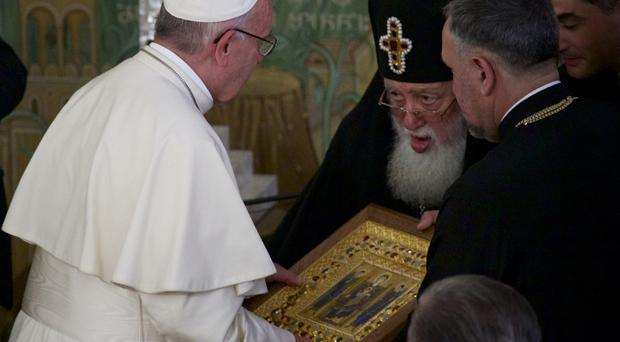 Georgian Orthodox Patriarch Iliya II, right, presents Pope Francis with an icon during their meeting in Tbilisi
