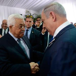 Israeli Prime Minister Benjamin Netanyahu shakes hands with Palestinian Authority President Mahmoud Abbas during the funeral