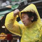A woman struggles against powerful gusts of wind generated by Typhoon Megi in Taipei (AP)