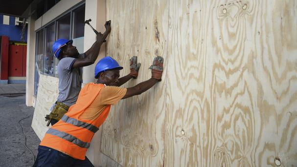 Worker nail a board to use on a shop window as protection against Hurricane Matthew in Kingston (AP)