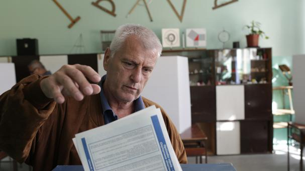 A Bosnian man casts his ballot at a polling station in Sarajevo (AP)