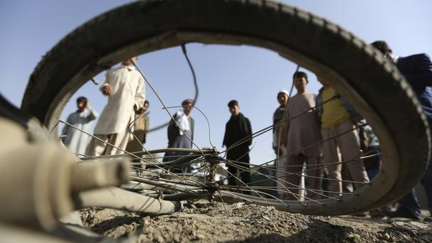 Afghan civilians view a damaged bicycle after a bomb explosion targeted an army vehicle in Kabul, Afghanistan, in a separate attack (AP)