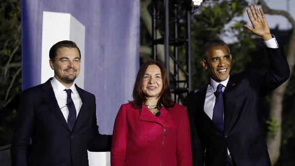 Barack Obama, right, arrives with Leonardo DiCaprio and Dr Katharine Hayhoe to talk about climate change at the White House event (AP)