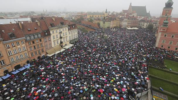 Thousands of people took part in the protest against stricter abortion laws in Warsaw, Poland, on Monday (AP)