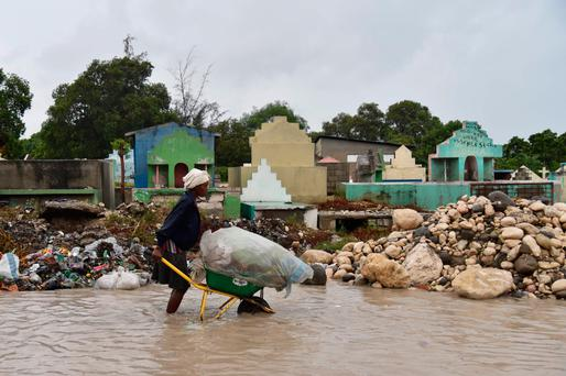 A woman pushes a wheelbarrow while walking in a partially flooded street, in the Haitian capital, Port-au-Prince. Photo: AFP/Getty Images