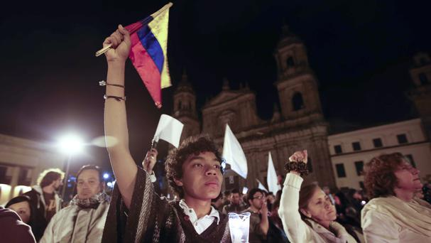 A youth holds a Colombian flag during the rally for peace in Bogota (AP)