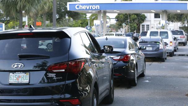 Motorists queue to buy petrol at a service station in Hollywood, Florida, during the mass exodus to escape the hurricane (AP)