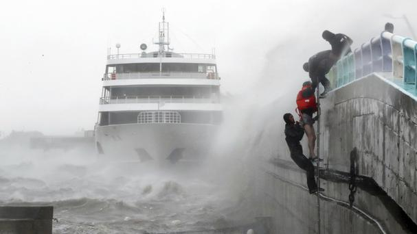 A crew member of a stranded passenger boat is rescued by maritime police in Yeosu (Yonhap/AP)