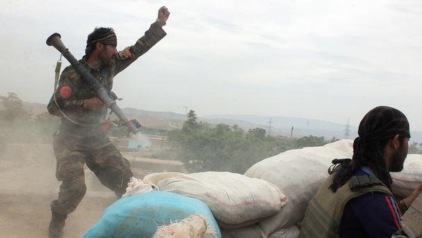 An Afghan National Army soldier shouts after firing a rocket towards Taliban positions on the outskirts of Kunduz (AP)