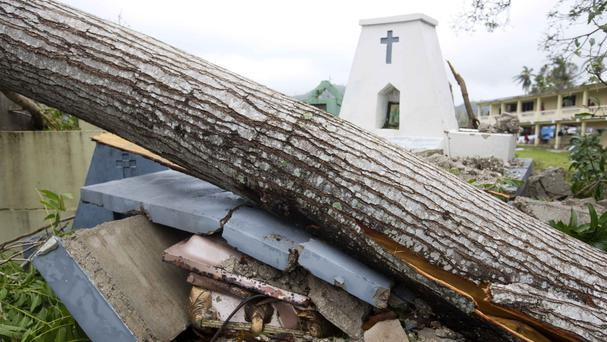 A tomb lies crushed by a tree felled by Hurricane Matthew in Camp Perrin, Haiti (AP)