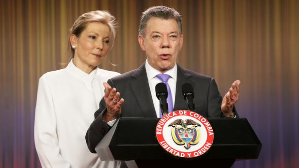 Juan Manuel Santos is accompanied by his wife as he speaks to the press at the presidential palace in Bogota (AP)