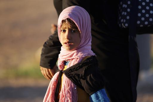 A girl who fled from Isil-controlled areas arrives in the northern Syrian rebel-held town of Waqf, near al-Rai town, Aleppo, Syria. Photo: Reuters/Khalil Ashawi.