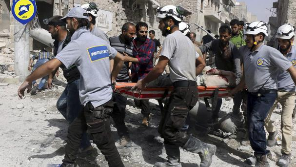 Rescue workers at the site of air strikes in the al-Sakhour neighbourhood of eastern Aleppo (Syrian Civil Defence White Helmets /AP)