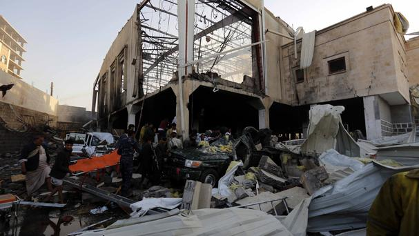 People inspect the aftermath of an air strike in Sanaa, Yemen (AP)