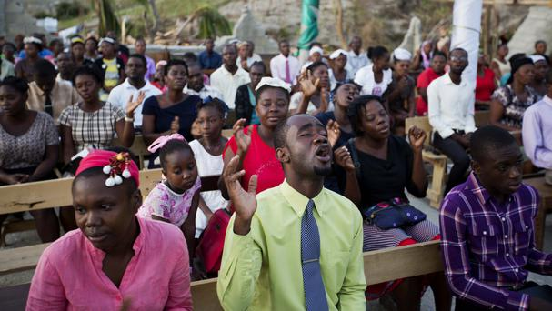 Residents pray at a church that was destroyed by hurricane Matthew in Jeremie, Haiti (AP)