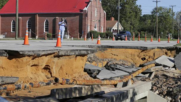 A man takes photos of a road damaged by floodwaters caused by rain from Hurricane Matthew in Fayetteville, North Carolina (AP)