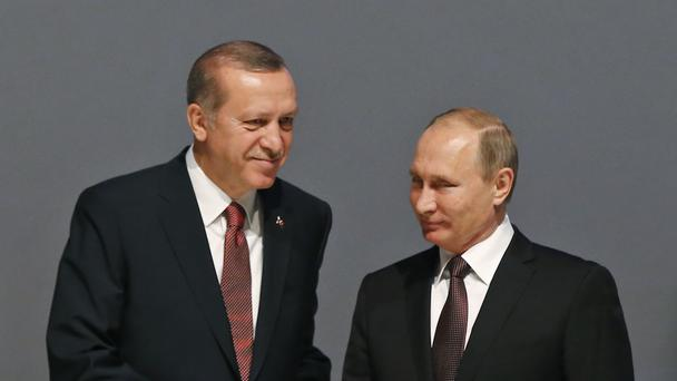 Turkish president Recep Tayyip Erdogan and Russian president Vladimir Putin shake hands following the group photo at the World Energy Congress in Istanbul (AP)