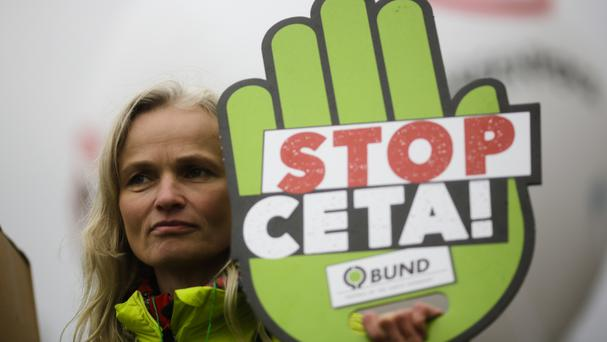 A demonstrator holds a poster against the Comprehensive Economic and Trade Agreement, CETA, during a protest in Berlin (AP)