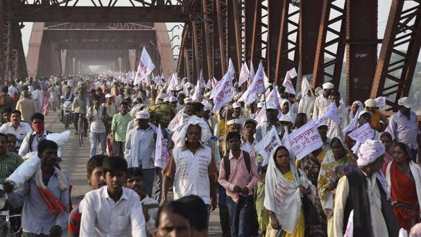 Hindu pilgrims hold religious flags and walk on a crowded bridge after a stampede on the same bridge on the outskirts of Varanasi, India (AP)