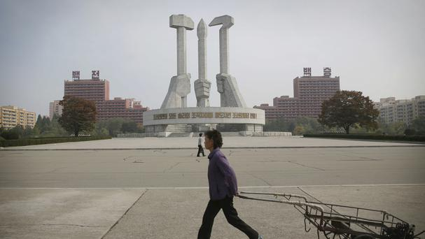 North Korean women walk past a monument built 11 years ago to honour the founding of the Workers' Party of North Korea (AP)