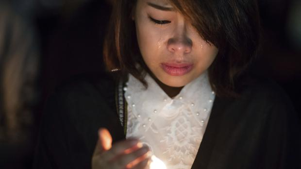 A Thai woman holds a candle outside the Grand Palace in Bangkok, as thousands of mourners paid their respects to the late King Bhumibol Adulyadej (AP)