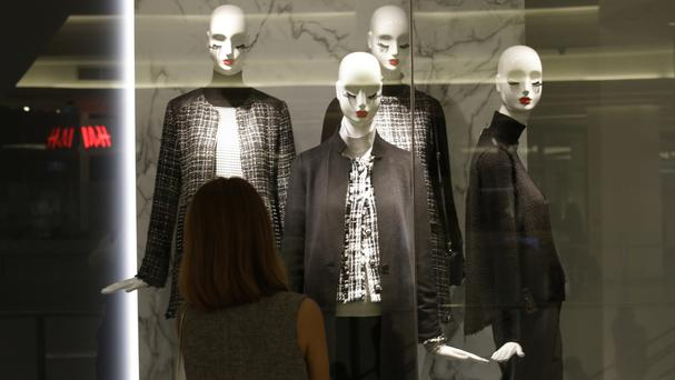 A woman views a display of mannequins wearing black and white clothing at a shopping centre in Bangkok, Thailand (AP)
